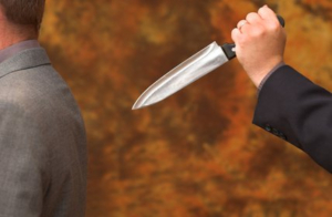 Businessman being stabbed in the back by traitor colleague or partner